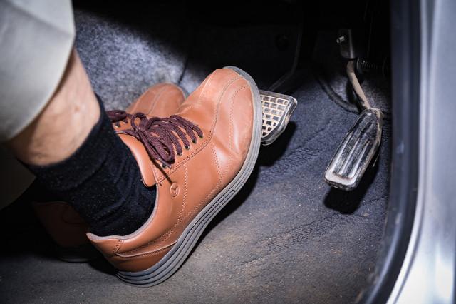 ブレーキを踏む人物の足